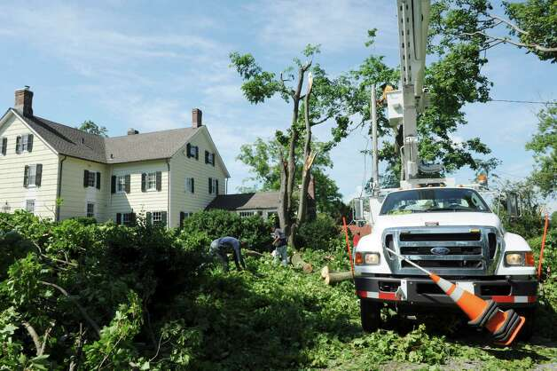 Tree service workers clear away tree limbs on a house on Nawthorne Road in Old Greenwich, Monday, Aug 6, 2012. A violent storm struck Greenwich Sunday night, knocking down trees and damaging homes, primarily in Old Greenwich. Photo: Helen Neafsey / Greenwich Time
