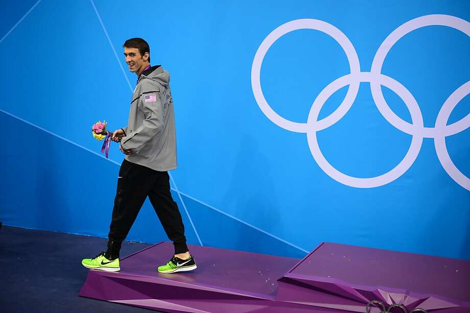 US swimmer Michael Phelps walks with a gold medal Friday. This year Nike's Flyknit shoe is scoring big on the medal stand and in the Olympic village. Photo: Martin Bureau, AFP/Getty Images