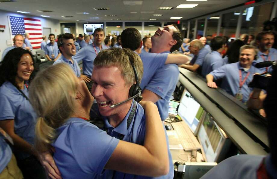 Telecom engineer Peter Ilott (C) hugs a colleague, celebrating a successful landing inside the Spaceflight Operations Facility for NASA's Mars Science Laboratory Curiosity rover at Jet Propulsion Laboratory (JPL) in Pasadena, California on August 5, 2012.  NASA's 2.5 billion USD Mars rover Sunday made a dramatic touchdown on the Red Planet, marking a successful end to the most sophisticated Mars attempt in history.       AFP PHOTO/Brian van der Brug/PoolBrian van der Brug/AFP/GettyImages Photo: Brian Van Der Brug, AFP/Getty Images