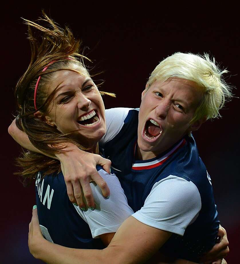 United States's midfielder Megan Rapinoe (R) celebrates with United States's forward Alex Morgan after scoring during the London 2012 Olympic Games womens semi final football match between USA and Canada at Old Trafford in Manchester, north-west England on August 6, 2012. AFP PHOTO / ANDREW YATESANDREW YATES/AFP/GettyImages Photo: Andrew Yates, AFP/Getty Images