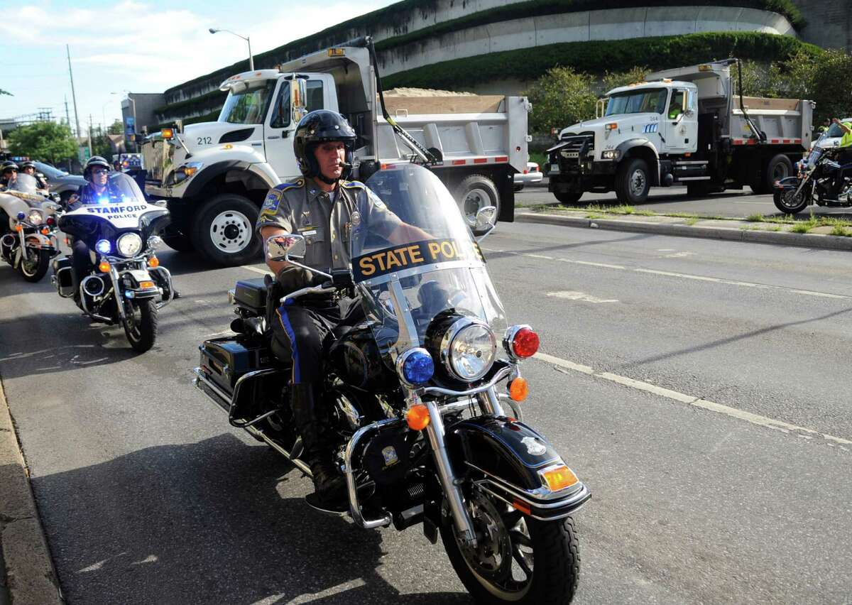 Police officers on motorcycles leave the Stamford Marriott after escorting President Barack Obama's motorcade on Monday, August 6, 2012.
