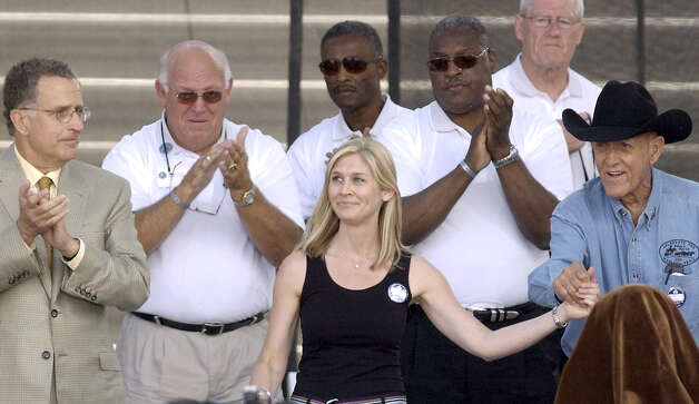 Marie Tillman, widow of Arizona Cardinals' Pat Tillman, who died during active duty in Afghanistan in April as a member of the U.S. Army, waves to the crowd prior to enshrinement ceremonies for the Class of 2004, at the Pro Football Hall of Fame on Sunday, Aug. 8, 2004, in Canton, Ohio. From left to right are, NFL Commissioner Paul Tagliabue, Billy Shaw, 1999 inductee, Paul Warfield, 1983 inductee, Art Shell, 1989 inductee, Jackie Smith, 1994 inductee, and former NFL player and war veteran Ralph Heywood. (AP Photo/The Repository, Scott Heckel)