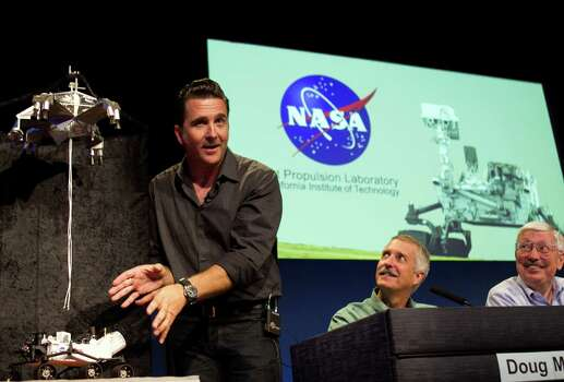 Adam Steltzner, Phase Lead and Development Manager for Entry, Descent, and Landing, JPL, left,  explains the Curiosity  rover's entry, descent, and landing (EDL) on Mars, during the Mission Engineering Overview news briefing at NASA's Jet Propulsion Laboratory in Pasadena, Calif., Thursday, Aug. 2, 2012. Smiling at right are: Doug McCuistion, Mars Exploration Program director, NASA Headquarters, center and Peter Theisinger, Manager of the MER Project at NASA's Jet Propulsion Laboratory. (AP Photo/Damian Dovarganes) Photo: Damian Dovarganes, Associated Press / AP