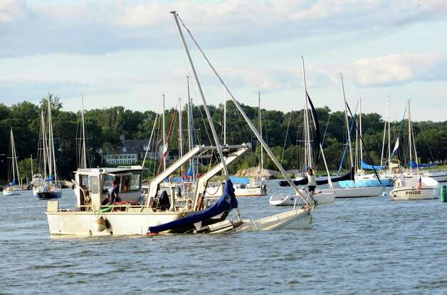 A sailboat being towed at Greenwich Cove Monday, Aug. 6, 2012, after being tossed about by a violent storm that struck Greenwich Sunday night. Photo: Helen Neafsey / Greenwich Time