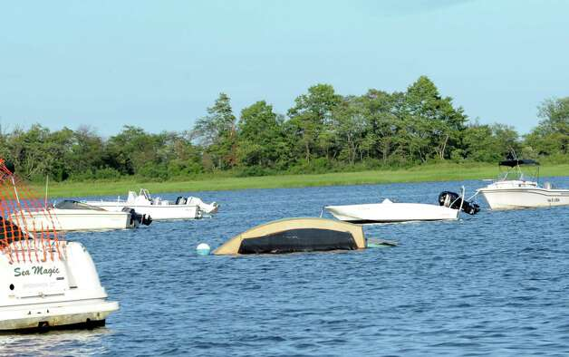 A boat partially underwater at Greenwich Cove Monday, Aug. 6, 2012, after being tossed about by a violent storm that struck Greenwich Sunday night. Photo: Helen Neafsey / Greenwich Time