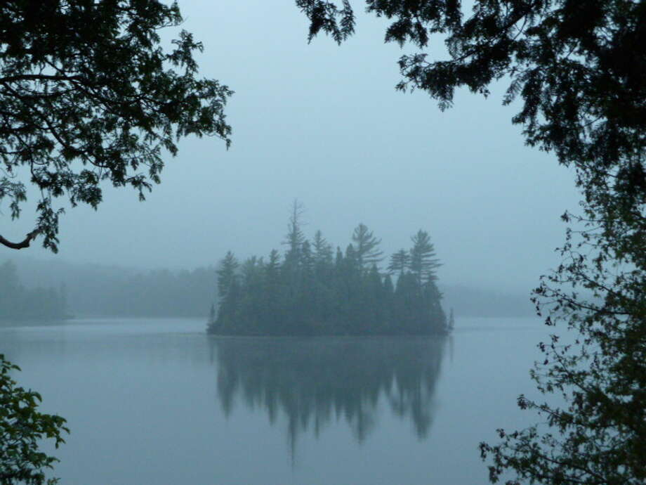 "Elk Lake Island is seen through the mist in a photo by Linda Kaplan taken from the porch of Little Tom Cabin at Elk Lake in North Hudson. ""One can hear the song of loons there,"" she says. ""I was also lucky to witness an eagle swoop down from a tree on the shoreline which was a huge thrill."" (Linda Kaplan)"