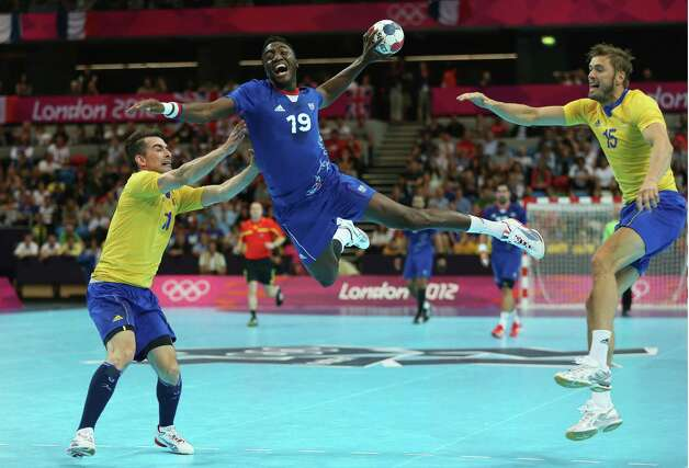 LONDON, ENGLAND - AUGUST 06: Luc Abalo of France jumps to shoot while Dalibor Doder (L) and Jonas Larholm (R) of Sweden can just watch on during the Men's Handball preliminaries group A match between France and Sweden on Day 10 of the London 2012 Olympic Games at the Copper Box on August 6, 2012 in London, England. Photo: Jeff Gross, Getty Images / 2012 Getty Images