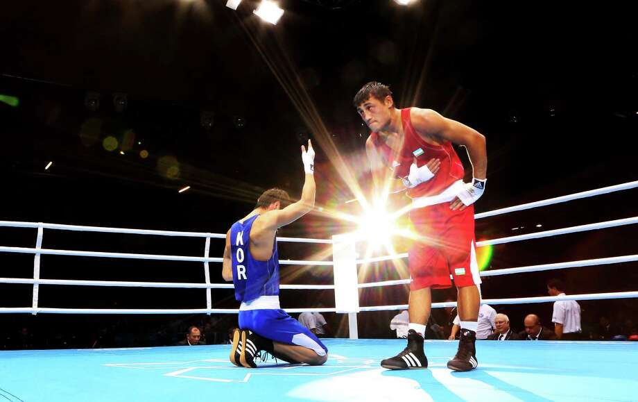 LONDON, ENGLAND - AUGUST 06:  Han Soonchul of Korea (L) celebrates his victory over Fazliddin Gaibnazarov of Uzbekistan during the Men's Light (60kg) Boxing on Day 10 of the London 2012 Olympic Games at ExCeL on August 6, 2012 in London, England. Photo: Scott Heavey, Getty Images / 2012 Getty Images