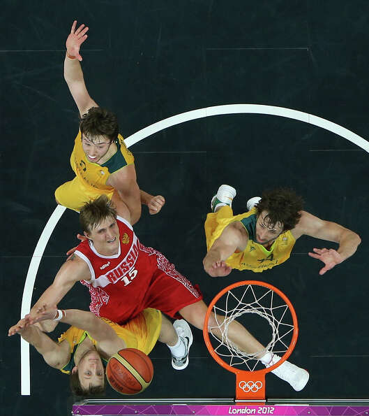 LONDON, ENGLAND - AUGUST 06: Andrei Kirilenko #15 of Russia is defended by Brad Newley #8, Matt Dell