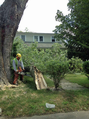 A worker cuts up a large tree branch Monday, Aug. 6, 2012, that ripped power lines down and fell on the roof of a home at 18 Grimes Road in Old Greenwich Sunday night, Aug. 5, 2012, cutting power to the home. Photo: Contributed Photo