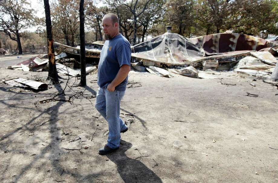 Bryan Butler stands at what is left of his grandparents' home which was destroyed by wildfires in Mannford, Okla.,  Monday, Aug. 6, 2012. Butler stayed as long as he could fighting the fire, but wasn't able to save the home. Three dozen wildfires have scorched portions of Oklahoma since Friday, leaving only ashes in some spots. (AP Photo/Tulsa World, Mike Simons) Photo: Mike Simons