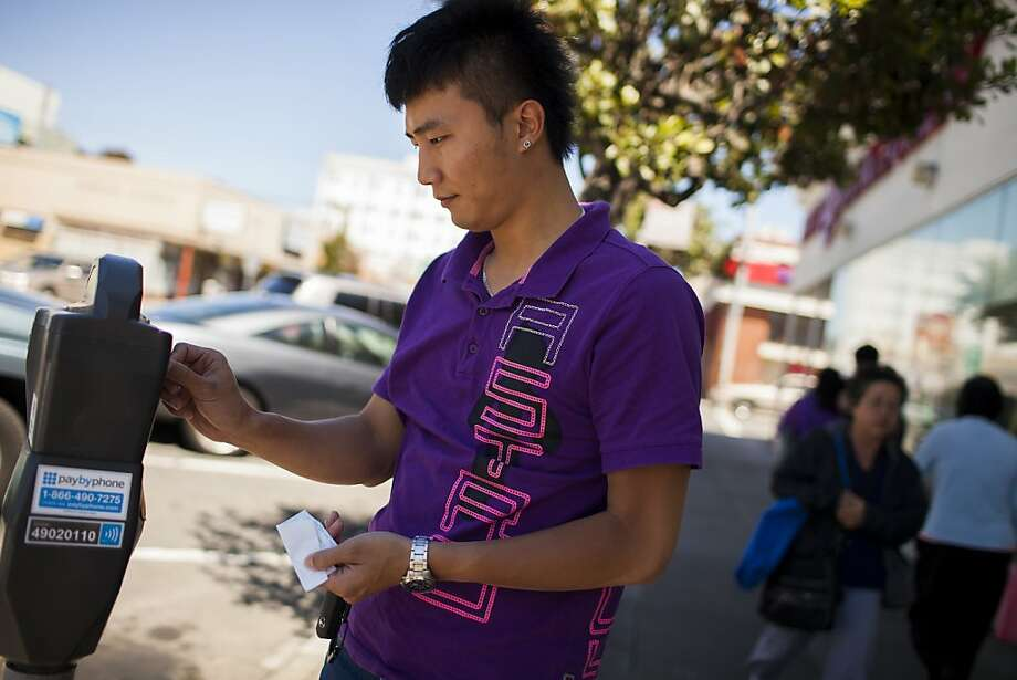 Ryan Zheng of San Francisco feeds a meter after parking his vehicle on Irving Street. Photo: Stephen Lam, Special To The Chronicle
