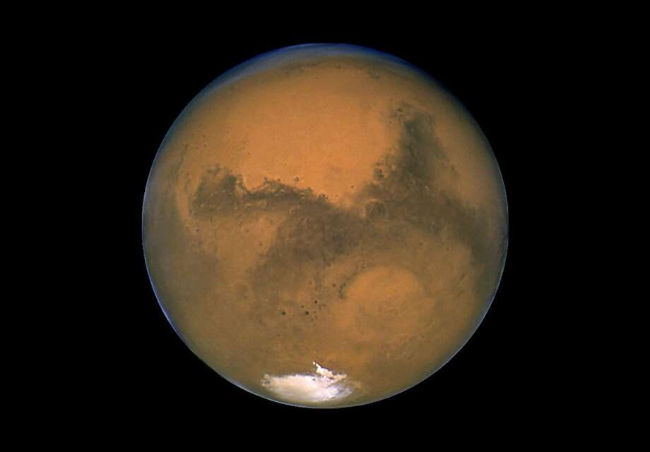 This Aug. 26, 2003 image made available by NASA shows Mars photographed by the Hubble Space Telescope on the planet's closest approach to Earth in 60,000 years. NASA's robotic rover Curiosity landed safely on Mars late Sunday, Aug. 5, 2012 to begin two years of exploration. The mission cost $2.5 billion. (AP Photo/NASA) Photo: Associated Press