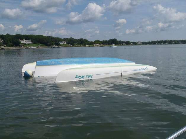A capsized boat at Greenwich Cove Monday, Aug. 6, 2012, after being tossed about by a violent storm that struck Greenwich Sunday night. Photo: Contributed Photo