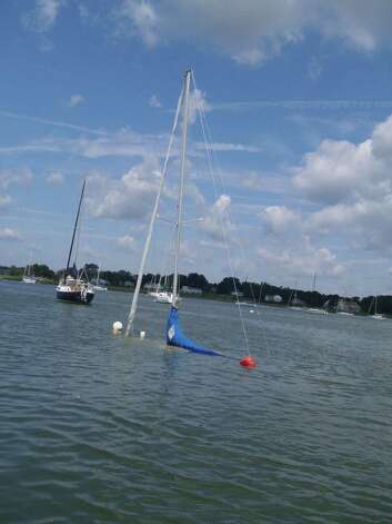 A submerged sailboat at Greenwich Cove Monday, Aug. 6, 2012, after being tossed about by a violent storm that struck Greenwich Sunday night. Photo: Contributed Photo
