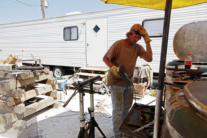BIZ - Welder Landy Trapp works on his welding truck while living at an RV Park on the outskirts of C