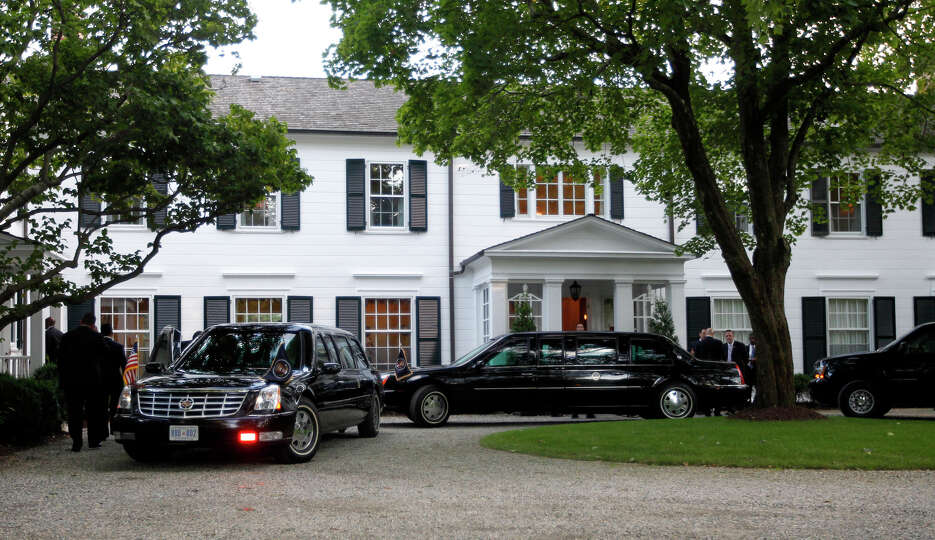 Limousines and motorcade vehicles for President Barack Obama are seen parked in the driveway outside