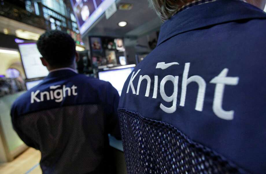 FILE - In this Friday, Aug. 3, 2012 file photo, Knight Capital specialists work at their posts on the floor of the New York Stock Exchange. Knight Capital announced Monday, Aug. 6, 2012, that investors have agreed to supply it with $400 million in financing, which would help the trading firm stay in business after last week's disastrous software glitch that shook U.S. stock trading and jeopardized its future. (AP Photo/Richard Drew, File) Photo: Richard Drew