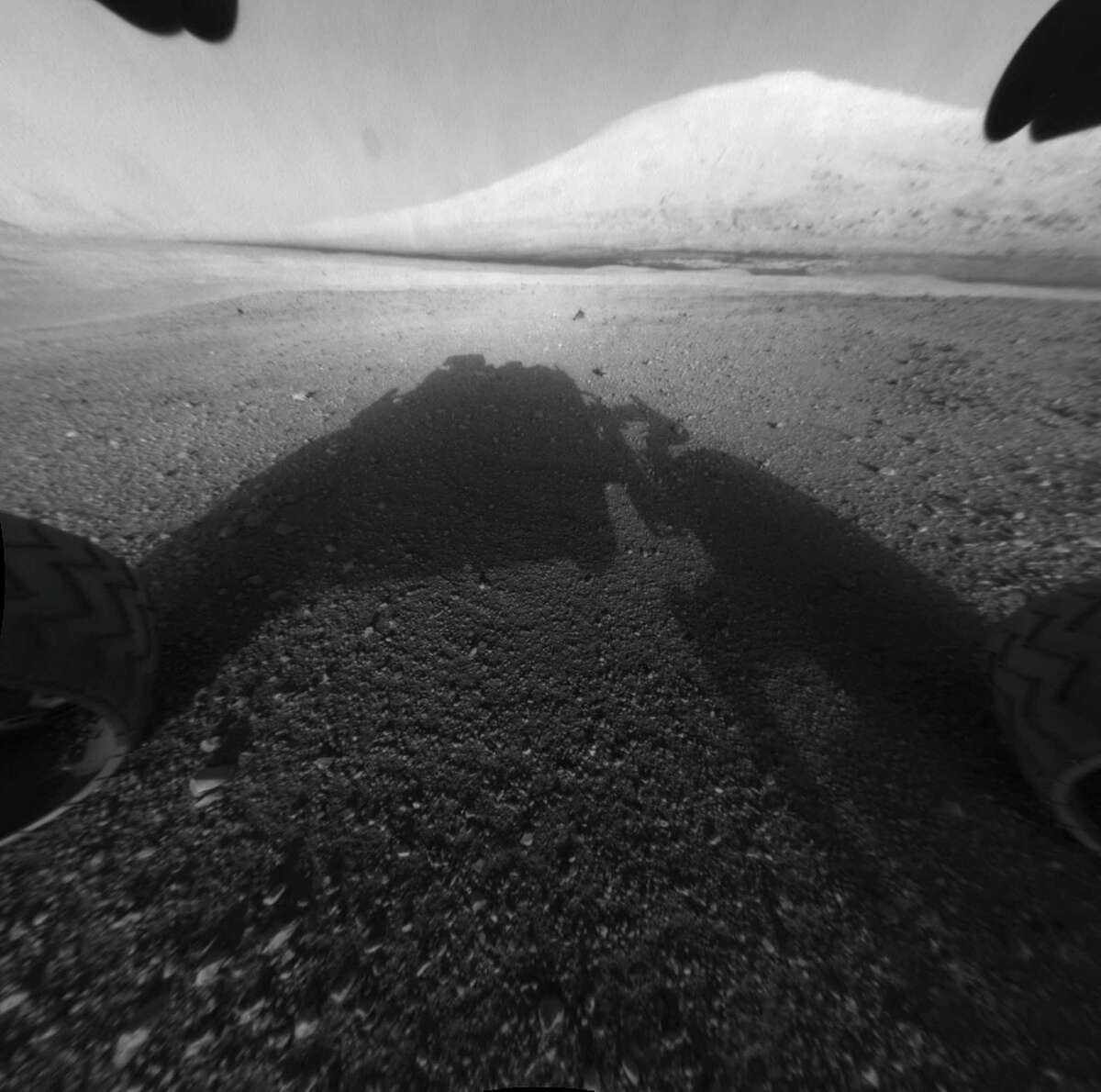 This image taken by NASA's Curiosity shows what lies ahead for the rover -- its main science target, informally called Mount Sharp Monday, Aug. 6, 2012. The rover's shadow can be seen in the foreground, and the dark bands beyond are dunes. Rising up in the distance is the highest peak of Mount Sharp at a height of about 3.4 miles (5.5 kilometers), taller than Mt. Whitney in California. The Curiosity team hopes to drive the rover to the mountain to investigate its lower layers, which scientists think hold clues to past environmental change. This image was captured by the rover's front left Hazard-Avoidance camera at full resolution shortly after it landed. It has not yet been linearized to remove the distorted appearance that results from its fisheye lens. (AP Photo/NASA/JPL-Caltech)