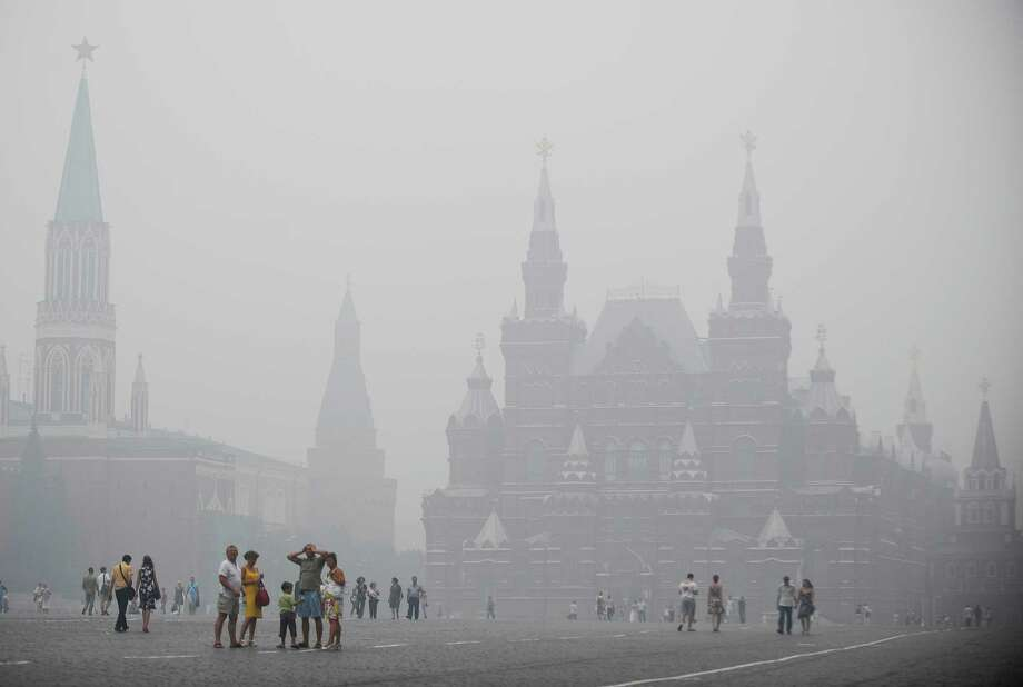 FILE -- Heavy smog from burning peat fires outside the Russian capital over visitors walking across the Red Square in Moscow, Aug. 4, 2010. A study says it is nearly certain that events like the Russian heat wave of 2010 would not have happened without the human release of greenhouse gases. (James Hill/The New York Times) -- NO SALES Photo: JAMES HILL / NYTNS
