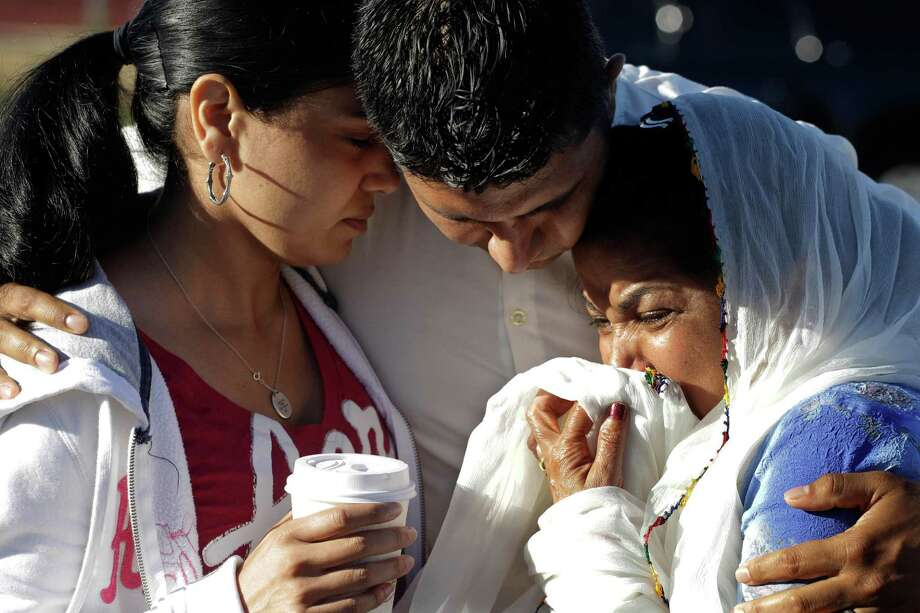 Amardeep Kaleka, son of the president of the Sikh Temple of Wisconsin, center, comforts members of the temple, Monday, Aug. 6, 2012, in Oak Creek, Wis., where a gunman killed six people a day earlier, before being shot and killed himself by police. Satwant Kaleka, 65, founder and president of the temple, died in the shooting. He was among four priests who died. (AP Photo/M. Spencer Green) Photo: M. Spencer Green