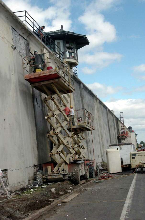 Workers repair a section of Clinton Correctional Facility's historic wall along Cook Street Sunday, Nov. 14, 2004, in Dannemora, N.Y. After four decades of harsh weather rotting the wooden wall and complaints from residents, New York state appropriated $20,000 to replace it with a more imposing barrier made from stones quarried in Dannemora and Lyon Mountain.  (AP Photo/Press Republican, Michael Betts) Photo: MICHAEL BETTS / PRESS REPUBLICAN