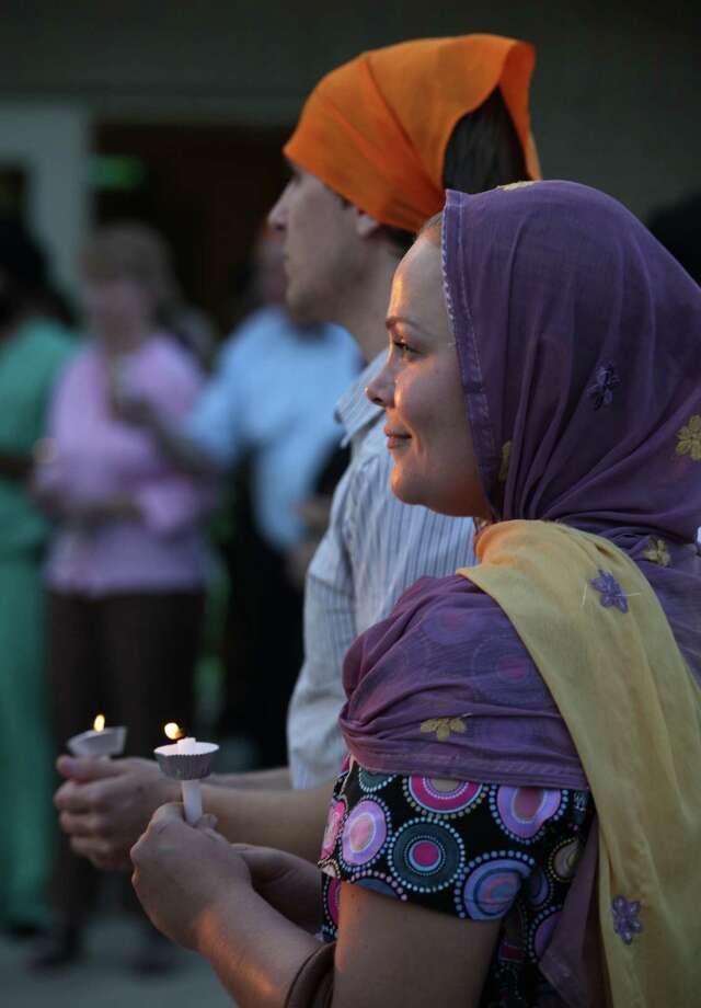 Addison Freeman, right, a Christian, and Lukman Ahmed, with red scarf, a Muslim, take part in a candlelight service at the Sikh Center of San Antonio, vigil for the Sikh members killed in a temple in Wisconsin.  Monday, Aug. 6, 2012. Photo: Bob Owen, San Antonio Express-News / © 2012 San Antonio Express-News