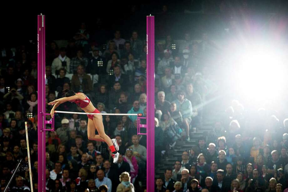 Jennifer Suhr of the USA is illuminated by the flash on a spectator's camera as she clears a height on her way to winning the gold medal in the women's pole vault final at the 2012 London Olympics on Monday, Aug. 6, 2012. Photo: Smiley N. Pool, Houston Chronicle / © 2012  Houston Chronicle