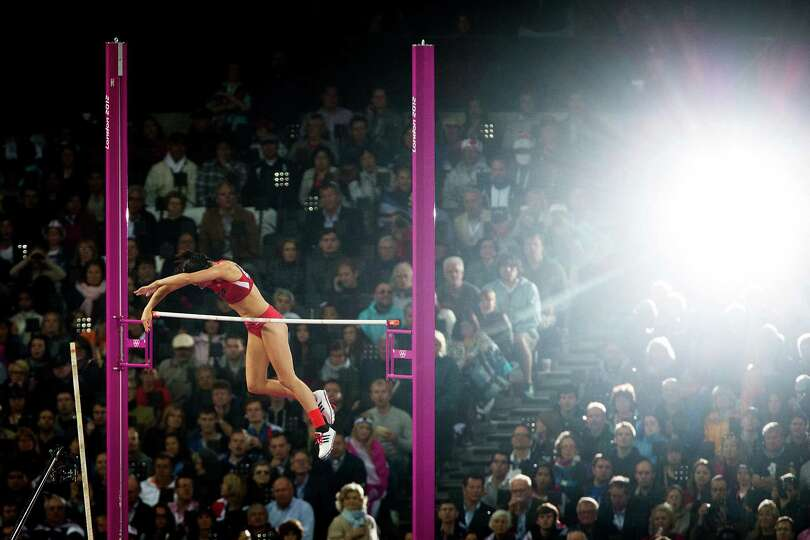 Jennifer Suhr of the USA is illuminated by the flash on a spectator's camera as she clears a height