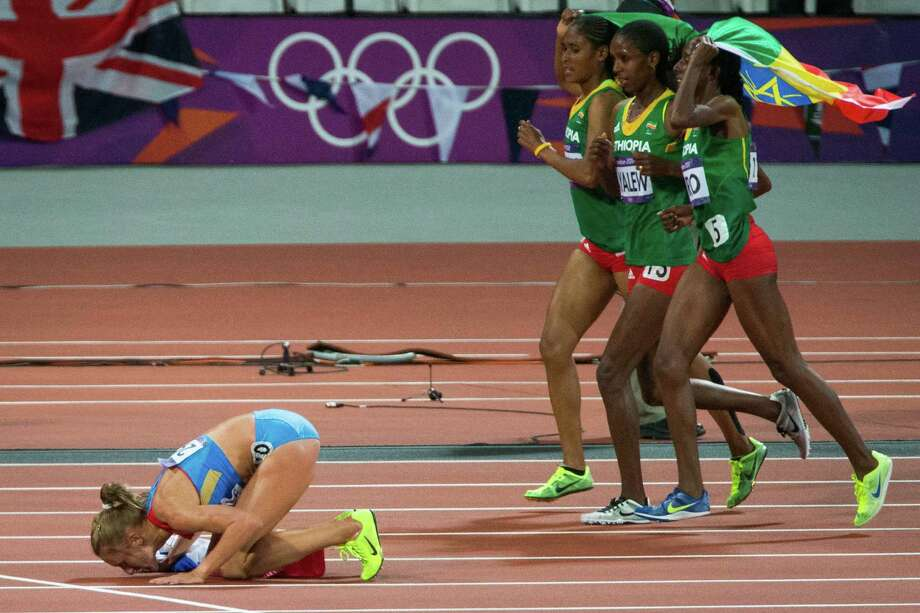 Yuliya Zaripova of Russia kisses the track at the starting line of the 3,000-meter women's steeplechase after winning the gold medal in the event at the 2012 London Olympics on Monday, Aug. 6, 2012. Behind her, the Ethiopia's Sofia Assefa, Hiwot Ayalew and Etenesh Diro take a victory lap to celebrate Assefa's bronze medal in the event. Photo: Smiley N. Pool, Houston Chronicle / © 2012  Houston Chronicle