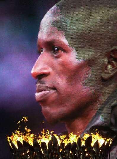 Men's 3000-meter steeplechase gold medalist Ezekiel Kemboi of Kenya is seen on a video screen above