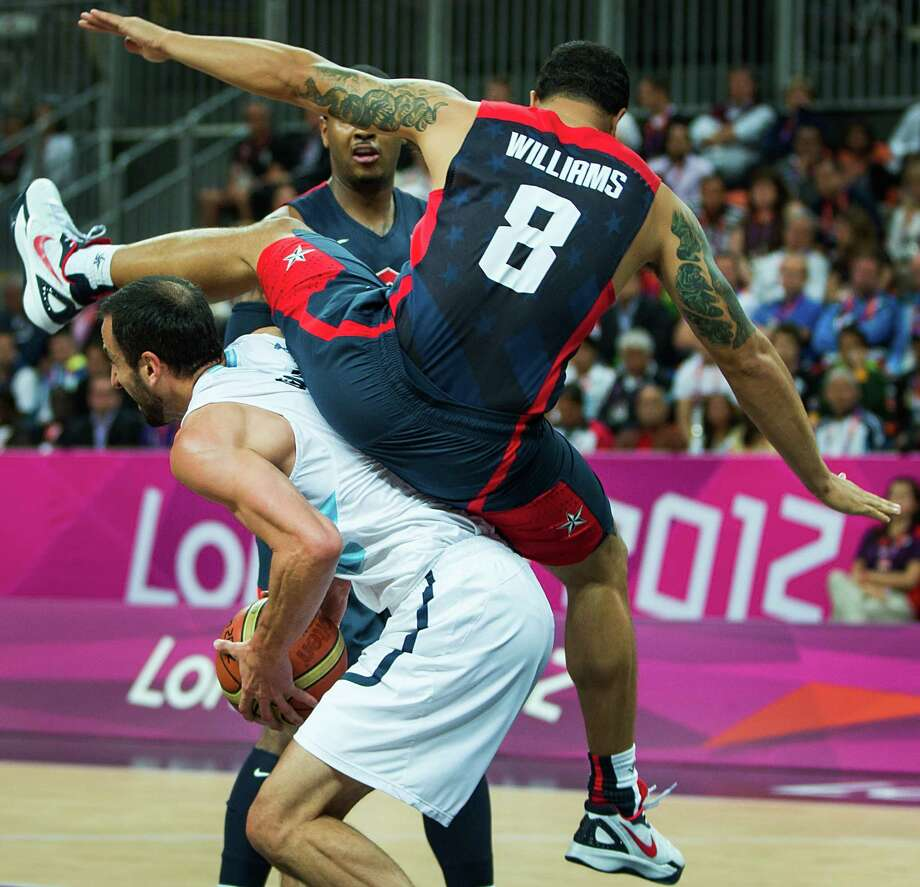 USA's Deron Williams comes down on top of Argentina's Manu Ginobili during a men's basketball preliminary round match at the 2012 London Olympics on Monday, Aug. 6, 2012. Photo: Smiley N. Pool, Houston Chronicle / © 2012  Houston Chronicle