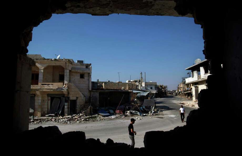 In this Sunday Aug. 5, 2012 photo,  Syrians are seen through a destroyed wall as they walk on a street in town of Atareb outskirts of Aleppo, Syria, Sunday, Aug. 5, 2012. (AP Photo) Photo: AP