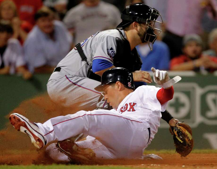 Boston Red Sox's Jacoby Ellsbury, front, scores on a double hit by Red Sox's Carl Crawford as Texas Rangers catcher Mike Napoli, behind, waits for the ball in the eighth inning of a baseball game at Fenway Park, in Boston, Monday, Aug. 6, 2012. (AP Photo/Steven Senne) Photo: Steven Senne