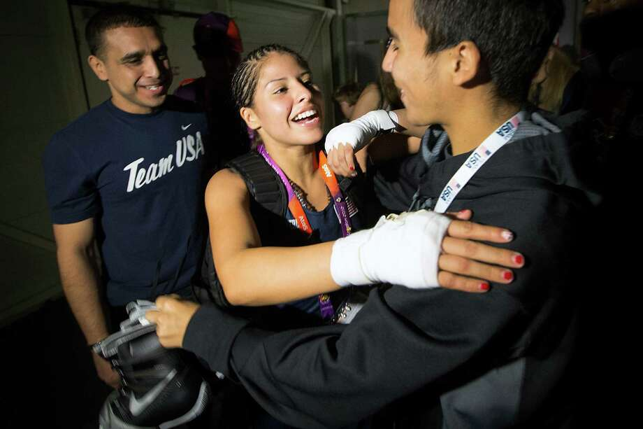 Among those celebrating Monday's victory with Pasadena boxer Marlen Esparza were sparring partner Gilbert Renteria (right) and coach Rudy Silva (left). Photo: Smiley N. Pool / © 2012  Houston Chronicle