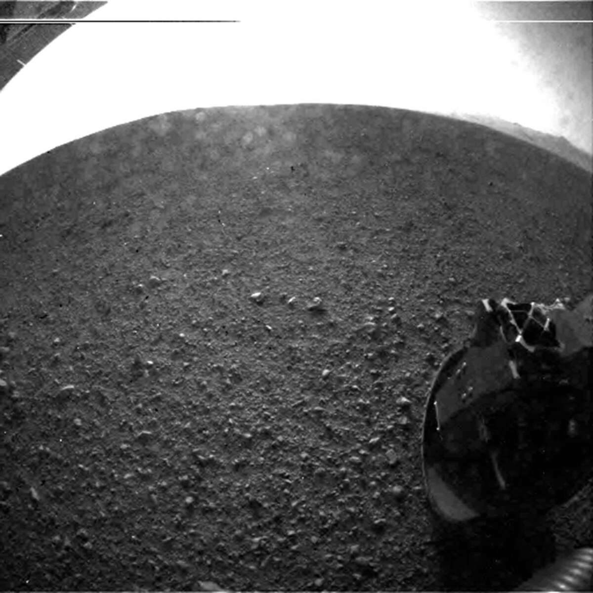 Gravel on the surface of Mars' Gale Crater is seen in this image taken by Curiosity. On the horizon is the rim of the crater. Part of the spring that released the lens' dust cover is at bottom right, near the rover's wheel. The lines at top are an artifact from the sensor since the camera is looking into the sun.
