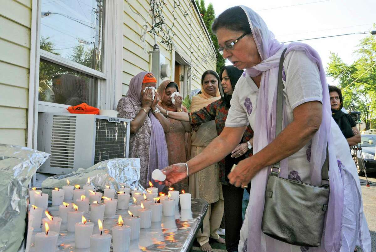 Veram Chahal lights a candle for the victims of Sunday's deadly shooting at a Sikh Gurudwara, or temple, in Wisconsin, at the East Greenbush Gurudwara on Monday evening Aug. 6, 2012 in East Greenbush, NY. Prakash K. Singh, far left, lost three members of her family in the attack. Her friend Parmjeet Paul is with her, second from left. (Philip Kamrass / Times Union)