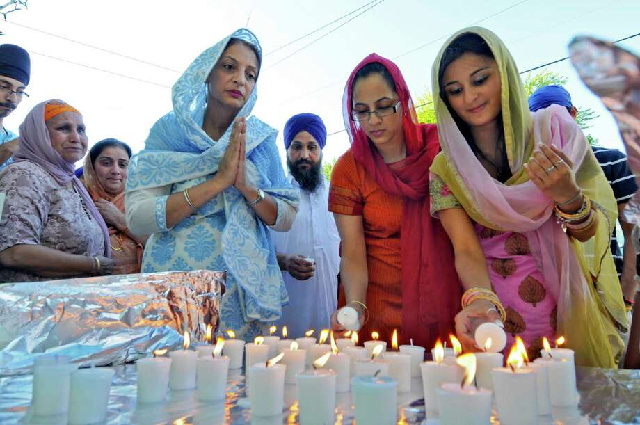 Renu Gujral, , fourth from right, Avneet Gujral, second from right, and Bani Sarang, right,  light candles for the victims of Sunday's deadly shooting at a Sikh Gurudwara, or temple, in Wisconsin, at the East Greenbush Gurudwara on Monday evening Aug. 6, 2012 in East Greenbush, NY.  Prakash K. Singh, second from left, lost three members of her family in the attack. Her friend Parmjeet Paul is with her, third from left. (Philip Kamrass / Times Union) Photo: Philip Kamrass / 00018733A