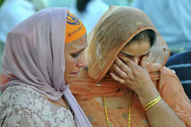 Prakash K. Singh, left, lost three members of her family in Sunday's deadly shooting at a Sikh Gurudwara, or temple, in Wisconsin, as she mourns them and waits to light candles at the East Greenbush Gurudwara on Monday evening Aug. 6, 2012 in East Greenbush, NY.  Her friend Parmjeet Paul is with her at right. (Philip Kamrass / Times Union) Photo: Philip Kamrass / 00018733A