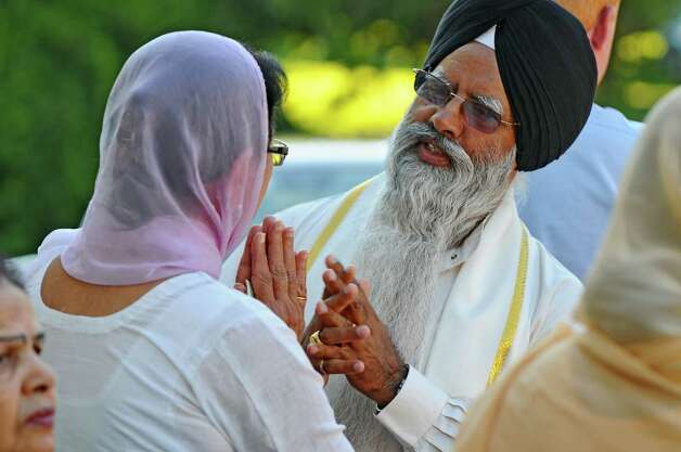 Gian Singh, right, a priest,  lost three members of his family in Sunday's deadly shooting at a Sikh Gurudwara, or temple, in Wisconsin. He talks with Veram Chahal, left, before he heads into the East Greenbush Gurudwara to resume a sangat, or fellowship, in memory of the victims on Monday evening Aug. 6, 2012 in East Greenbush, NY.  (Philip Kamrass / Times Union) Photo: Philip Kamrass / 00018733A