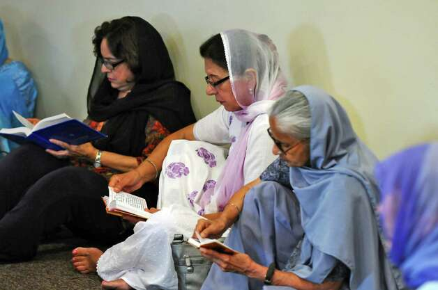 Women listen as Gian Singh,  a priest, who lost three members of his family in Sunday's deadly shooting at a Sikh Gurudwara, or temple, in Wisconsin leads a sangat, or fellowship, in the East Greenbush Gurudwara in memory of the victims on Monday evening Aug. 6, 2012 in East Greenbush, NY.  (Philip Kamrass / Times Union) Photo: Philip Kamrass / 00018733A