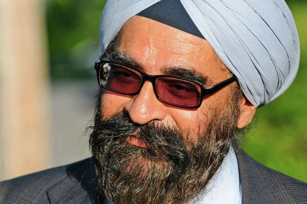 Dr. Arvinder Singh, President of the Sikh Association of the Capital District, talks about  Sunday's deadly shooting at a Sikh Gurudwara, or temple, in Wisconsin before a sangat, or fellowship, in the East Greenbush Gurudwara in memory of the victims on Monday evening Aug. 6, 2012 in East Greenbush, NY.  (Philip Kamrass / Times Union) Photo: Philip Kamrass / 00018733A
