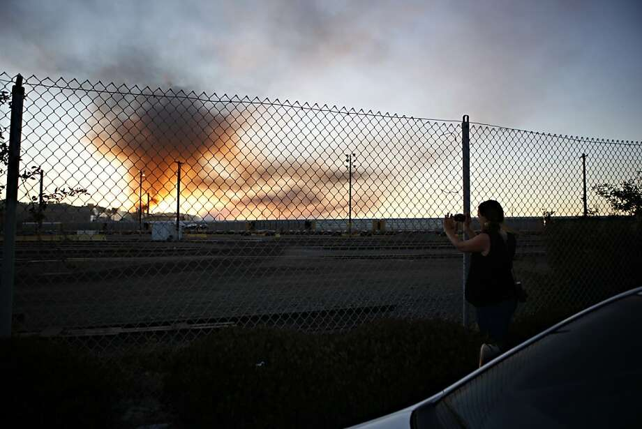 Elizabeth Fein, of El Cerrito, takes a photo of plumes of smoke emanating from the Chevron oil refinery on Monday, August 6, 2012 in Richmond, Calif. Photo: Beck Diefenbach, Special To The Chronicle