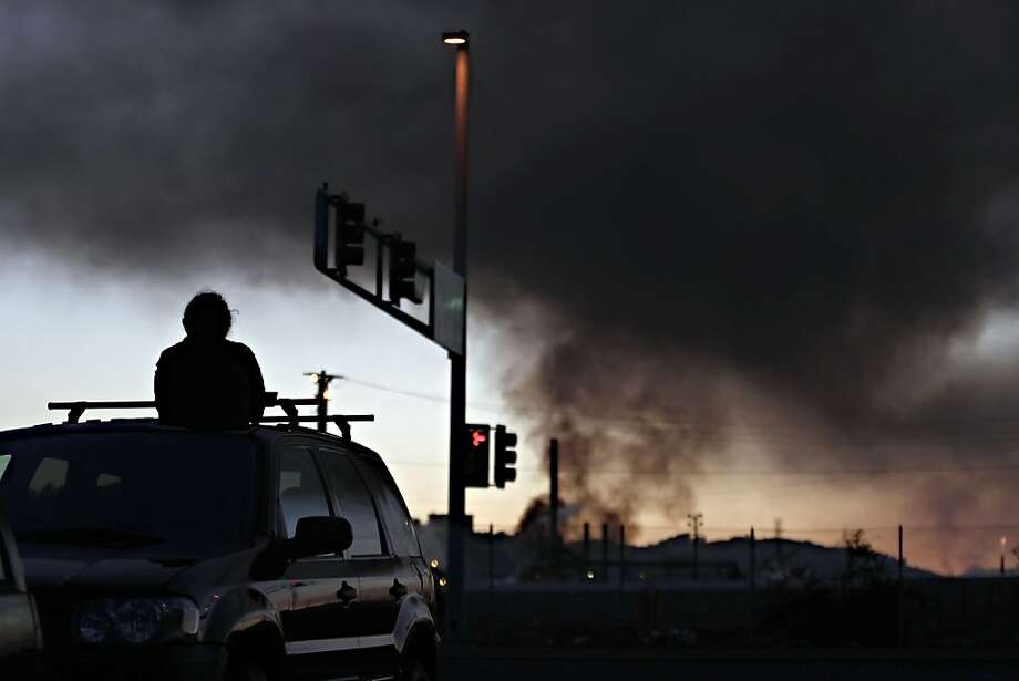 "Marce Gutierrez, of Hercules, watches of plumes of smoke emanate from the Chevron oil refinery on Monday, August 6, 2012 in Richmond, Calif. ""I'm just trying to figure out if we need to leave,"" Gutierrez said. Photo: Beck Diefenbach, Special To The Chronicle"