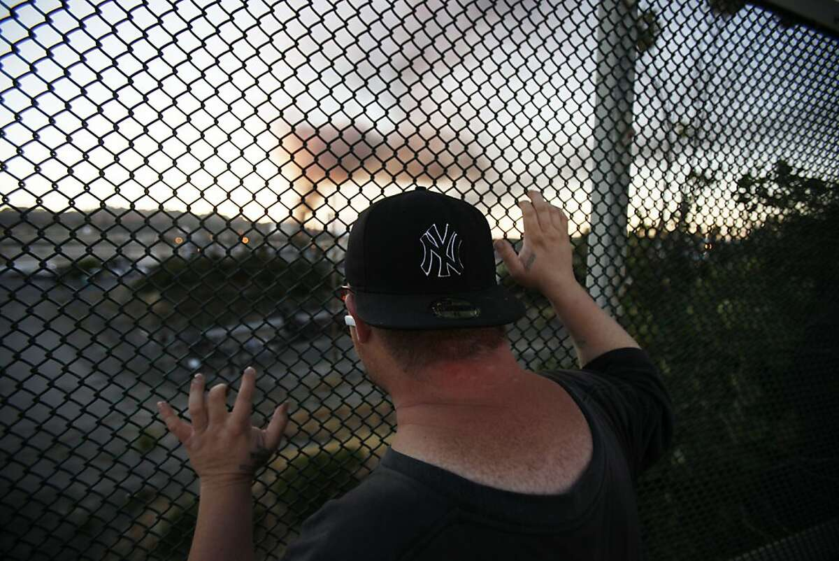 John Smith, of Richmond, watches the Chevron Oil Refinery fire from a distance through a fence on Castro Road in Richmond, Calif. on Monday, Aug. 6, 2012.