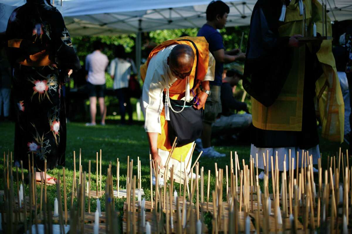 Br. Senji Kanaeda of the Nipponzan Myohoji Dojo picks out a latern during the From Hiroshima to Hope latern ceremony held at Green Lake on Monday, Aug. 6, 2012. From Hiroshima to Hope is an annual Lantern Floating Ceremony which is held to promote peace and remember victims of Hiroshima/Nagasaki and all victims of war.
