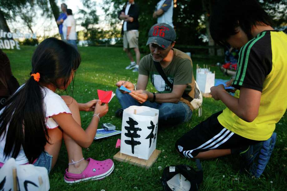Kurumi, Seiya, and Kaenji Miyazaki make origami figures during the From Hiroshima to Hope Latern Ceremony held at Green Lake on Monday, Aug. 6, 2012. From Hiroshima to Hope is an annual Lantern Floating Ceremony which is held to promote peace and remember victims of Hiroshima/Nagasaki and all victims of war. Photo: Sofia Jaramillo / SEATTLEPI.COM