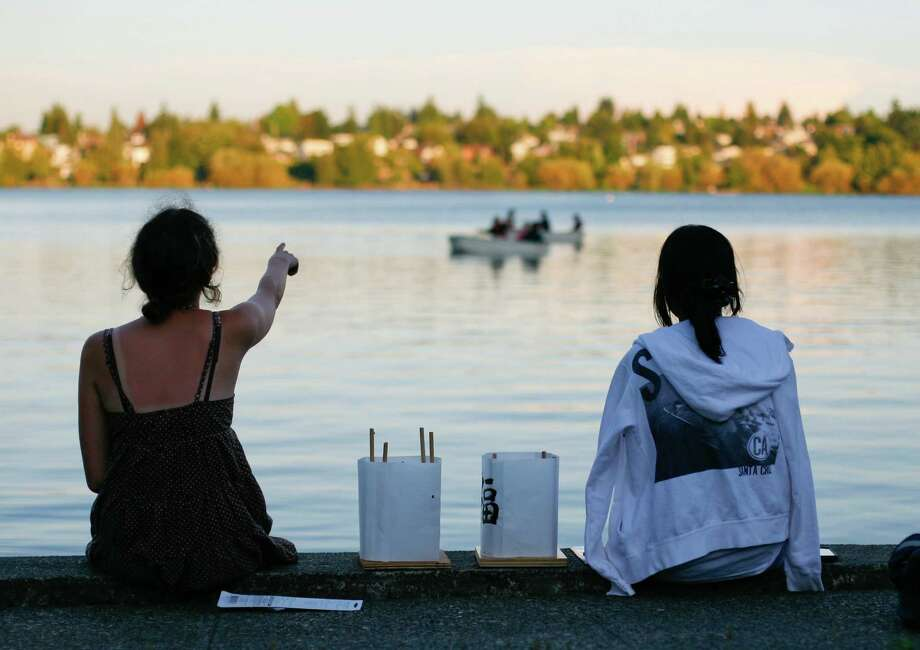 Samantha Romanelli and Aslie Juan watch boats as they wait to set their lanterns in the water before the From Hiroshima to Hope Latern Ceremony held at Green Lake on Monday, Aug. 6, 2012. From Hiroshima to Hope is an annual Lantern Floating Ceremony which is held to promote peace and remember victims of Hiroshima/Nagasaki and all victims of war. Photo: Sofia Jaramillo / SEATTLEPI.COM