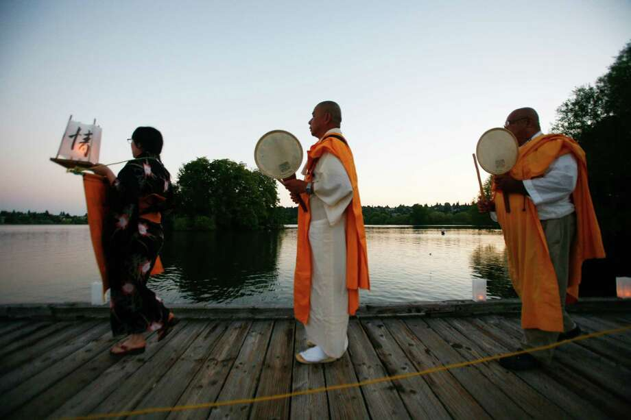 Br. Senji Kanaeda (middle) and others lead a procession to the launching dock during the From Hiroshima to Hope Latern Ceremony held at Green Lake on Monday, Aug. 6, 2012. From Hiroshima to Hope is an annual Lantern Floating Ceremony which is held to promote peace and remember victims of Hiroshima/Nagasaki and all victims of war. Photo: Sofia Jaramillo / SEATTLEPI.COM