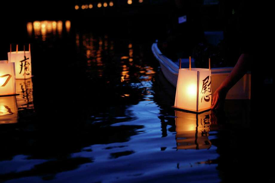 Cathy Tuttle puts a lantern into the water during the From Hiroshima to Hope Latern Ceremony held at Green Lake on Monday, Aug. 6, 2012. From Hiroshima to Hope is an annual Lantern Floating Ceremony which is held to promote peace and remember victims of Hiroshima/Nagasaki and all victims of war. Photo: Sofia Jaramillo / SEATTLEPI.COM